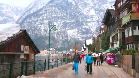 mercado : HALLSTATT, AUSTRIA - FEBRUARY 21, 2019: Tourists walk Seestrasse lakeside promenade, lined with old living houses, cafes and souvenir stores, on February 21 in Hallstatt