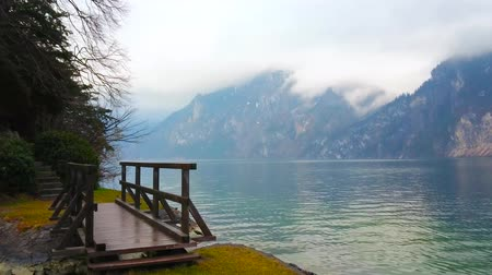 falu : The tiny bridge at Badeinsel recreational zone with a view on Traunsee lake and rainy clouds, stuck on Traunstein mountain, Traunkirchen, Salzkammergut, Austria