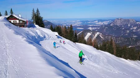 trilhas : ST GILDEN, AUSTRIA - FEBRUARY 23, 2019: The skiers go uphill along the snowy slope of Zwolferhorn mount, the famous winter resort in Salzkammergut, on February 23 in St Gilden