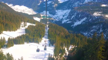 trilhas : GOSAU, AUSTRIA - FEBRUARY 26, 2019: The modern gondolas of Panorama Jet Zwieselalm cableway runs over the mountain slope and overlooks spectacular Alpine  anture, on February 26 in Gosau