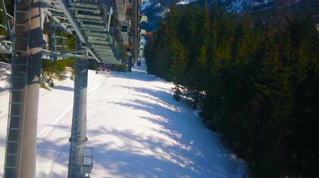 trilhas : GOSAU, AUSTRIA - FEBRUARY 26, 2019: Panorama Jet Zwieselalm cable car offers the journey with a view on snowy mountain slope, spruce forest and perfect ski pistes, on February 26 in Gosau