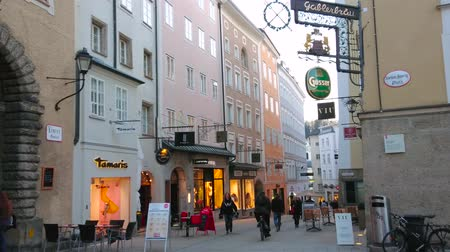 znamení : SALZBURG, AUSTRIA - FEBRUARY 27, 2019: Evening walk through the busy Linzergasse street with tourist stores and cafes, on February 27 in Salzburg