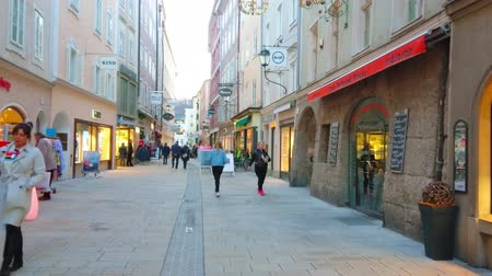 historical : SALZBURG, AUSTRIA - FEBRUARY 27, 2019: Popular tourist Linzergasse street is lined with old edifices, housing cafes, beer bars, fashion stores and art galleries, on February 27 in Salzburg