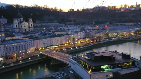 torre : Dusk panorama of Altstadt district of Salzburg, Hohensalzburg castle and Salzach river from the top of Kapuzinenberg hill, Austria Stock Footage