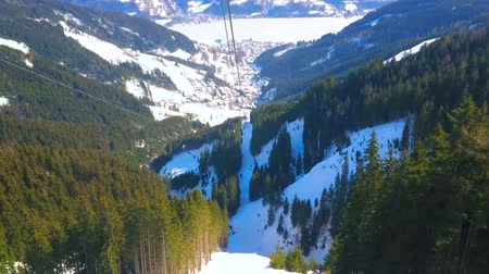 air vehicle : Schmittenhohe mountain cableway overlooks the stunning nature of Zell am See, frozen Zeller see (lake) in valley, tall fir trees, snowy Alpine slopes and ski trails, Austria Stock Footage