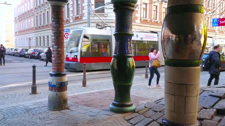 trimestre : VIENNA, AUSTRIA - FEBRUARY 19, 2019: The view on modern tram, ridind through the Lowengasse street through the unusual porcelain columns of Hundertwasserhaus, on February 19 in Vienna