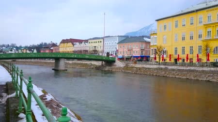 avusturya : BAD ISCHL, AUSTRIA - FEBRUARY 20, 2019: Historical green bridge of Kaiserin Elizabeth, connecting the banks of Traun river, occupied with historical buildings, on February 20 in Bad Ischl Stok Video