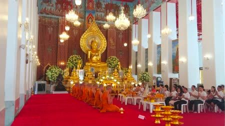 semt : BANGKOK, THAILAND - APRIL 23, 2019: The worship in Ubosot of Wat Chana Songkhram monastery, decorated with gilt image f Buddha, carved and painted wood, flowers and garlands, on April 23 in Bangkok Stok Video