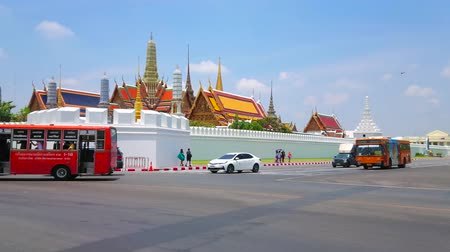 kruispunt : BANGKOK, THAILAND - APRIL 23, 2019: Panorama of busy road at Grand Palace fortress wall with rising tile roofs, chedis and prangs of the temples and Royal buildings, on April 23 in Bangkok