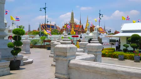 torre : BANGKOK, THAILAND - APRIL 23, 2019: Grounds of City Pillar Shrine open the view on Grand Palace buildings - chedis, tile roofs and Royal Pantheon with prang summit, on April 23 in Bangkok Stock Footage