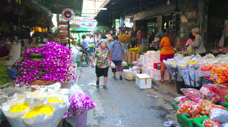 composição : BANGKOK, THAILAND - APRIL 23, 2019: The narrow shady alleyway of Pak Khlong Talat flower market with wide range of cut flowers in small shops on both sides, on April 23 in Bangkok Stock Footage
