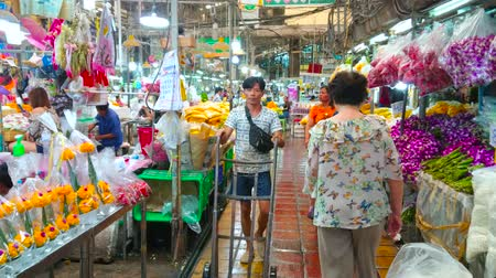 composição : BANGKOK, THAILAND - APRIL 23, 2019: Interior of Pak Khlong Talat flower market with narrow alleyway, surrounded by colorful fresh flowers, bouquets, garlands and decorations, on April 23 in Bangkok Stock Footage