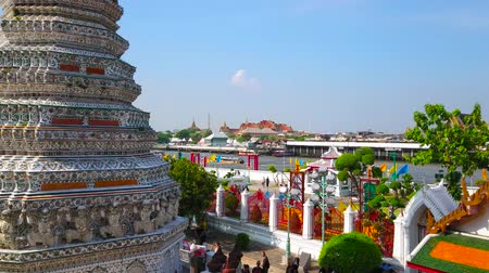 torre : BANGKOK, THAILAND - APRIL 23, 2019: Thonburi bank of Chao Phraya river with a view on ornate faience-covered prang of Wat Arun, pier and Grand Palace roofs on the opposite bank, on April 23 in Bangkok Stock Footage