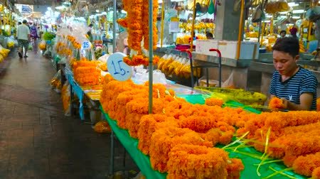 composição : BANGKOK, THAILAND - APRIL 23, 2019: The vendor makes ritual marigold garlands in small stall of Pak Khlong Talat flower market, on April 23 in Bangkok