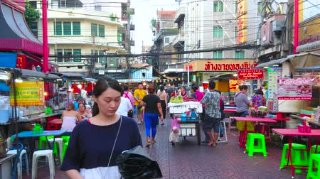 yaowarat road : BANGKOK, THAILAND - APRIL 23, 2019: The crowded alley at Yaowarat road of Chinatown with many small cafes, restaurants, street food carts and shops, on April 23 in Bangkok Stock Footage