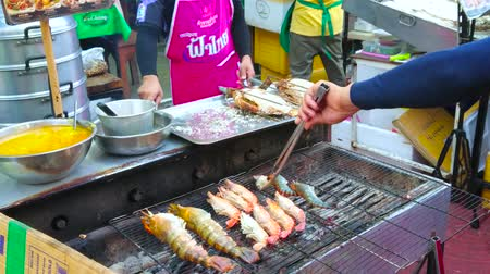 chinatown : BANGKOK, THAILAND - APRIL 23, 2019: De koks maken vis, octopussen en garnalen op de grill in de open luchtkeuken van het café in Yaowarat road, Chinatown, op 23 april in Bangkok