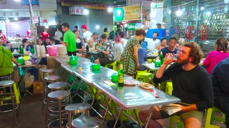 grillowanie : BANGKOK, THAILAND - APRIL 23, 2019: The busy roadside restaurant in Yaowarat avenue with wide range of Chinese and Thai dishes, cool drinks, on April 23 in Bangkok