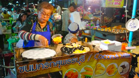 grillowanie : BANGKOK, THAILAND - APRIL 23, 2019: The street food vendor cooks coconut pudding pancakes in a small stall of Khao San night market, on April 23 in Bangkok