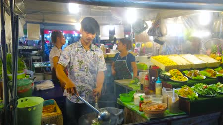 kuchnia : PATONG, THAILAND - MAY 1, 2019: The chef of small cafe cooks stir fry vegetables  in open air kitchen of Bangla streets food court, on May 1 in Patong