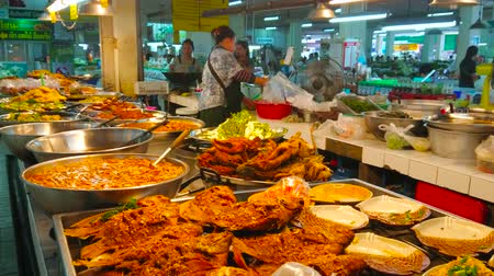 mercado : CHIANG MAI, THAILAND - MAY 4, 2019: The  food stalls of Tanin market offer tasty takeaway foods, such as deep fried fish, vegetables and seafood on wok, soups and sauces, on May 4 in Chiang Mai