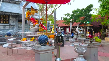 histórico : CHIANG MAI, THAILAND - MAY 4, 2019: The altar of Ganesha shrine with chatra umbrella and floral garlands, located on Silver Temple (Wat Sri Suphan) grounds, on May 4 in Chiang Mai