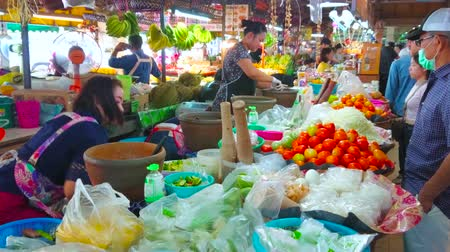 mercado : CHIANG MAI, THAILAND - MAY 4, 2019: The salads, made with mortar and pestle are popular in Thai cuisine, they are widespread in food stalls and cafes of Tanin market, on May 4 in Chiang Mai