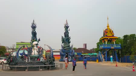 украшенный : CHIANG RAI, THAILAND - MAY 10, 2019: Court of Wat Rong Seua Ten (Blue Temple) with fountain, belfry and gate, richly decorated with stucco reliefs, sculptures and patterns, on May 10 in Chiang Rai
