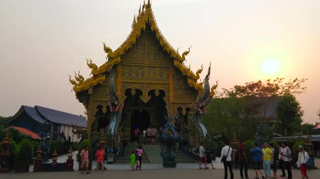 украшенный : CHIANG RAI, THAILAND - MAY 10, 2019: Sunset over amazing viharn of Wat Rong Seua Ten (Blue Temple), decorated with pyathat roof, chofa decors, gilt, Naga serpents guardians, on May 10 in Chiang Rai
