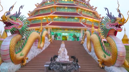 crepúsculo : The small image of Guan Yin (Goddess of Mercy) and bowl with incense sticks in front of the pagoda with two giant Naga dragons, Wat Huai Pla Kang, Chiang Rai, Thailand
