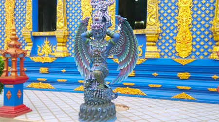 patronen : The beautiful statue of Garuda bird-like creature, located at the side wall of Wat Rong Seua Ten (Blue Temple) viharn, next to the mondops (tiny pavilions), Chiang Rai, Thailand