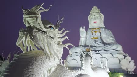 sudeste : The giant white statue of Guan Yin (Goddess of Mercy), sitting on the big lotus on hilltop with a view on dragons head (Naga serpent) on the foreground, Wat Huai Pla Kang, Chiang Rai, Thailand