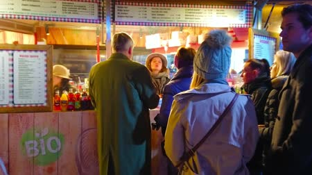 adil : VIENNA, AUSTRIA - FEBRUARY 18, 2019: The line of clients at the small food stall, offering hot traditional meals at winter fair, on February 18 in Vienna Stok Video