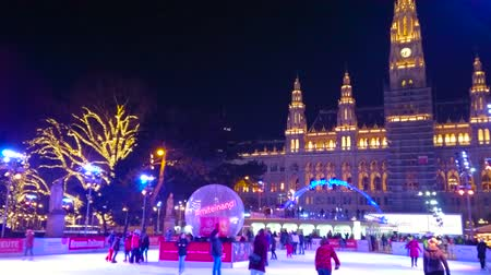 historical : VIENNA, AUSTRIA - FEBRUARY 18, 2019: The ice skating rink in bright evening lights and Town Hall (Rathaus) building on background, on February 18 in Vienna.