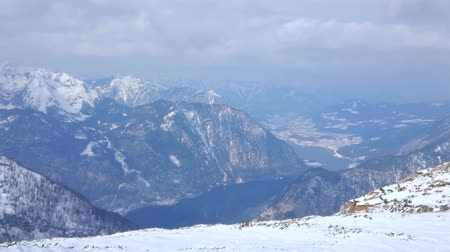 hegytömb : Krippenstein mountain peak overlooks the misty valley of Hallstattersee lake and snowy Alps of Dachstein massif, Obertraun, Salzkammergut, Austria Stock mozgókép