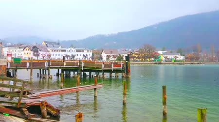 паром : GMUNDEN, AUSTRIA - FEBRUARY 22, 2019: Walk the foggybank of Traun lake (Traunsee) and watch empty wooden pier and poles for boats, on February 22 in Gmunden