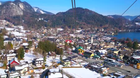 torre : ST GILGEN, AUSTRIA - FEBRUARY 23, 2019: The birds eye view of the tourist town, lower air lift station, Wolfgangsee lake and Inner Salzkammergut Alps on background, on February 23 in St Gilgen Stock Footage
