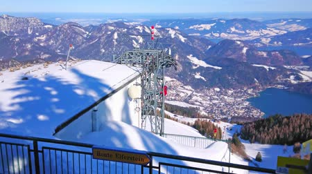 torre : ST GILGEN, AUSTRIA - FEBRUARY 23, 2019: The view on riding air lift,  snowy mountains and Wolfgangsee lake from the viewing platform behind the upper cableway station, on February 23 in St Gilgen