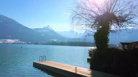 torre : The sunny winter day is perfect to relax on embankment of Wolfgangsee lake and enjoy idyllic Alpine nature, St Wolfgang, Salzkammergut, Austria Stock Footage