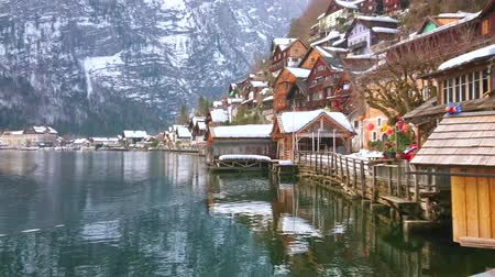 historical : HALLSTATT, AUSTRIA - FEBRUARY 25, 2019: Relax on embankment of Hallstatter see (lake) and watch reflection of old town and Alpine slopes in clear lakes surface, on February 25 in Hallstatt Stock Footage