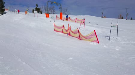 trilhas : EBENSEE, AUSTRIA - FEBRUARY 24, 2019: The gentle snowy slope of Feuerkogel mountain is used as the kids ski zone with equipment for training and curved piste, on february 24 in Ebensee Vídeos