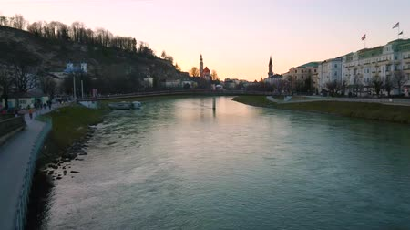 avusturya : SALZBURG, AUSTRIA - FEBRUARY 27, 2019: Nice riverside cityscape with amazing lights of sunset over the Monchsberg hill, on February 27 in Salzburg
