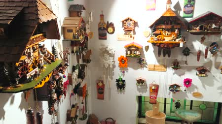 zegar : ZELL AM SEE, AUSTRIA - FEBRUARY 28, 2019: The walls of souvenir shop are covered with traditional handmade cuckoo clocks with tiny carved figurines and reliefs, on February 28 in Zell Am See.