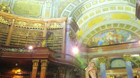 historical : VIENNA, AUSTRIA - MARCH 2, 2019: The splendid frescoes on the dome in the Prunksaal Hall of National Library and marble sculpture of Emperor Charles VI in Roman clothes, on March 2 in Vienna
