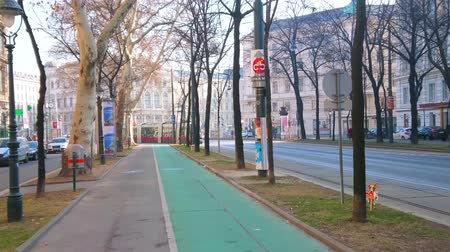historical : VIENNA, AUSTRIA - FEBRUARY 18, 2019: Watch the modern red tram, riding along the trees and historical edifices of famous Ringstrasse avenue, on February 18 in Vienna.