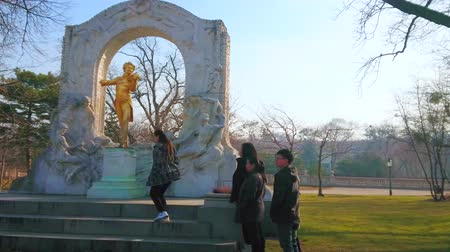 historical : VIENNA, AUSTRIA - FEBRUARY 18, 2019: The tourists stand in queue at the Golden Strauss statue in City park to make selfies and pictures, on February 18 in Vienna. Stock Footage