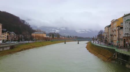 mozart : SALZBURG, AUSTRIA - MARCH 1, 2019: The misty rainy weather in city, clouds gather around Alpine peaks, seen behind the Salzach river and Mozart bridge, on March 1 in Salzburg