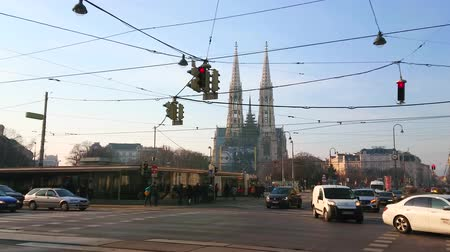 torre : VIENNA, AUSTRIA - FEBRUARY 18, 2019: The maze of electric wires over Ringstrasse avenue with a view on people and transport activity in front of  Votivkirche (Votive Church), on February 18 in Vienna. Stock Footage
