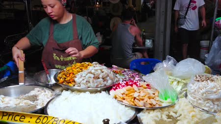 mercado : BANGKOK, THAILAND - APRIL 23, 2019: The young vendor of Khao San night market cooks traditional Thai dishes with steamed seafood, fish, noodles, vegetables, herbs and spices, on April 23 in Bangkok Stock Footage