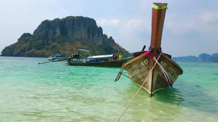 praia : AO NANG, THAILAND - APRIL 26, 2019: The rocking longtail boat is moored on the shallow beach of Koh Tup Island in front of rocky Koh Poda Island, on April 26 in Ao Nang