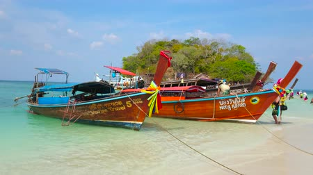sziget : AO NANG, THAILAND - APRIL 26, 2019: The longtail boats are moored along the sand spit, connecting Koh Tup and Koh Mor Islands, on April 26 in Ao Nang Stock mozgókép